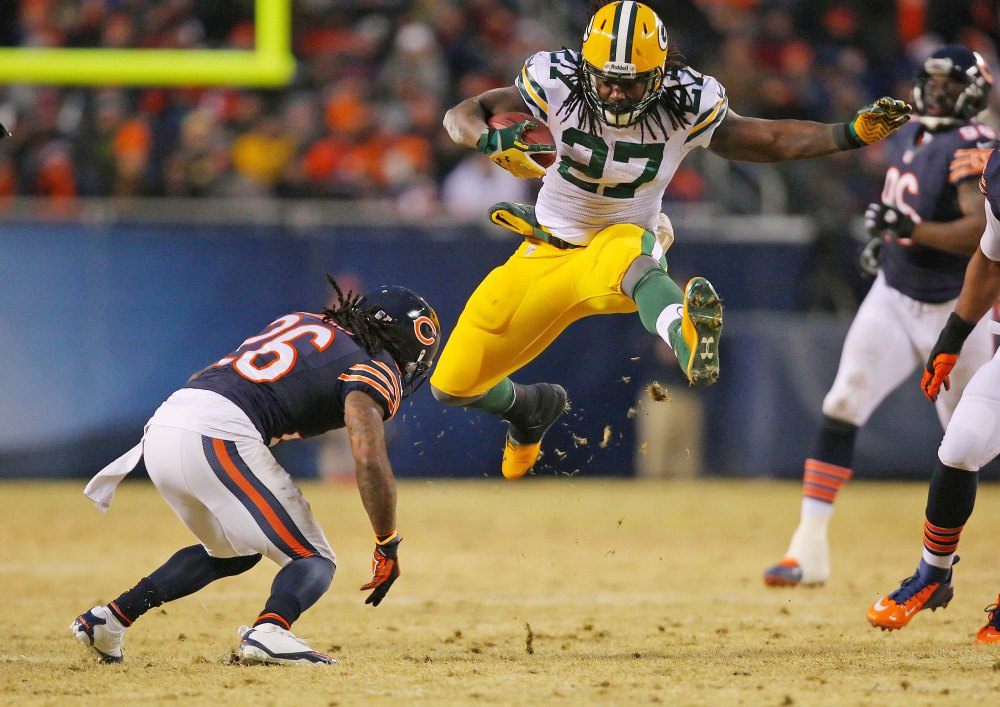 Dec 29, 2013; Chicago, IL, USA; Green Bay Packers running back Eddie Lacy (27) leaps over Chicago Bears cornerback Tim Jennings (26) during the second quarter at Soldier Field. Mandatory Credit: Dennis Wierzbicki-USA TODAY Sports